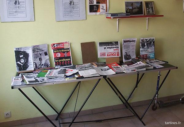 Une table dans un coin de la boulangerie, avec des tracts, des prospectus et autres pamphlets pro-anarcho-communistes syndicalistes. On a un peu de tout, ça va du NPA en passant par Arlette ou CNT...